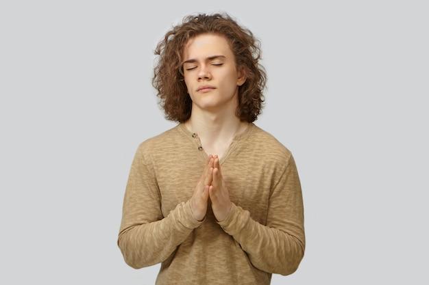 긴팔 셔츠에 매력적인 희망을 부드럽게 면도 한 젊은 백인 남성의 허리까지 눈을 감고기도하거나 명상하는 동안 손바닥을 함께 누르면 격리 된 서