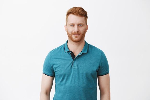 Снимок талии привлекательного мужественного мужчины с рыжими волосами в зеленой рубашке-поло, ухмыляющегося и смотрящего с уверенным и самоуверенным выражением лица, чувствуя себя спокойно