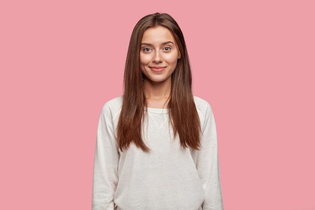 Снимок привлекательной молодой девушки с темными прямыми волосами, мягкой здоровой кожей с талией вверх