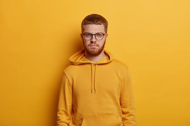 あごひげを生やした生姜男のウエストアップショットは、直接見て、厳格な自信を持って表現し、眼鏡とパーカーを着て、学生は黄色の壁に隔離された大学で講義に来ます