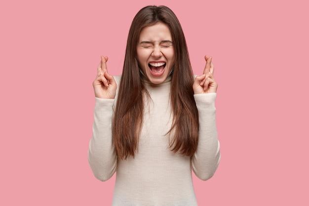 Снимок с талией красивой женщины, держащей пальцы в жесте надежды, просит о чем-то важном, желает, чтобы мечты сбывались, одетая в белый джемпер