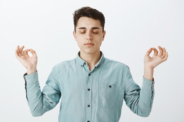 Спокойный, сосредоточенный европейский парень в модной рубашке с увеличенной талией