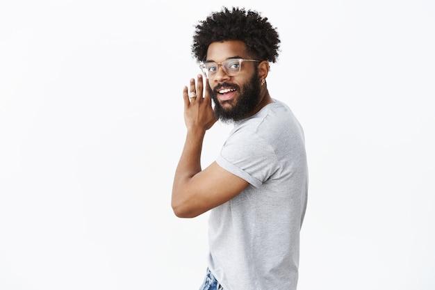 Снимок беззаботного, счастливого, эмоционального и харизматичного темнокожего бородатого мужчины в очках, размахивающего руками и поворачивающегося в камеру с позитивной улыбкой, танцующего под хорошую музыку у серой стены