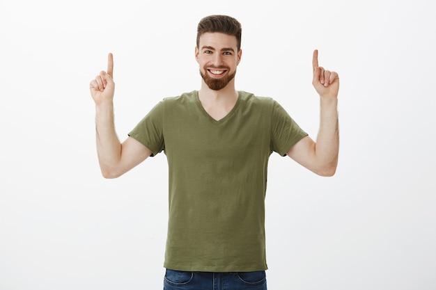 オリーブのtシャツにひげを生やして人差し指で上向きのカリスマ的な白人男性の上半身ショット。白い壁に幸せな表情で喜んで喜んで笑顔