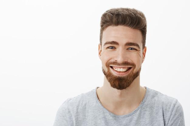 Снимок талии очаровательного беззаботного и оптимистичного красавца с бородой, усами и милыми голубыми глазами, радостно смеющегося, щурясь от радости и веселья, веселящегося у серой стены