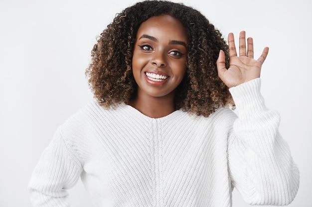魅力的なフレンドリーな見た目の楽観的な浅黒い肌の女性が挨拶で手のひらを上げて手を振る、または白い壁の上のカフェで友達に会うと広く笑っている挨拶ジェスチャーのウエストアップショット