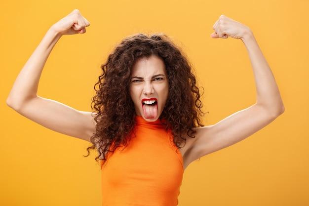 クールで大胆な白人女性のオレンジ色のトップのウエストアップショット。腕の眉をひそめているタトゥーで、舌を上げて舌を突き出し、筋肉が力と強さを感じていることを示す変な顔をしています。コピースペース