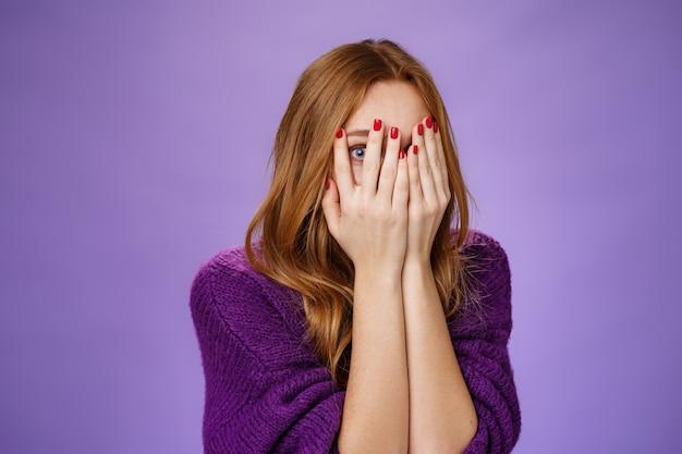 紫色の背景の上で次に何が起こるかに興味を持って指から覗くホラー映画を見ながら、恐怖から手のひらで顔を覆っている好奇心旺盛でかわいい赤毛の女性のウエストアップショット。