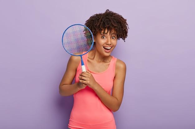 기쁘게 아프리카 계 미국인 여자의 허리까지 총은 테니스 라켓을 보유하고 친구가 토너먼트를 갖기를 기다립니다.