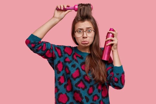 음침한 표정으로 불쾌한 젊은 여성의 허리 위로 샷, 아랫 입술 지갑, 혼자서 머리를 만들고, 무언가를 좋아하지 않습니다.