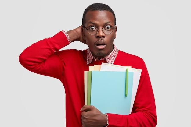 감정적 인 흑인 청년의 허리 샷은 당황하여 머리를 긁적이며 어두운 피부를 가지고 있으며 시험 준비 마감일을 실현합니다.