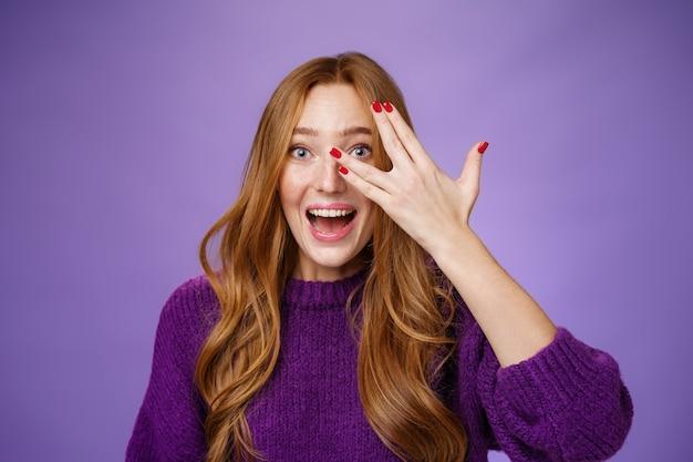 熱狂的でカリスマ的なかわいい面白い赤毛の女性の紫色のセーターのウエストアップショット。クールな爪が指の穴から覗き、楽観的で興奮して驚いて笑っています。