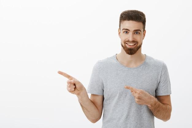 Снимок талии восторженного и харизматичного красивого спортсмена с бородой и белой приятной улыбкой, указывающего влево обоими пальцами, взволнованно улыбающегося, предлагая прохладную копию пространства на серой стене