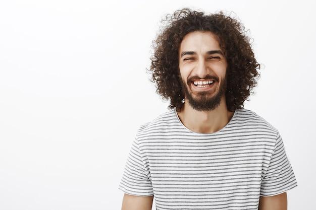 スタイリッシュなストライプのtシャツを着て、うれしそうに大声で笑う、巻き毛のある優しい幸せなヒスパニックのひげを生やした男の上半身ショット