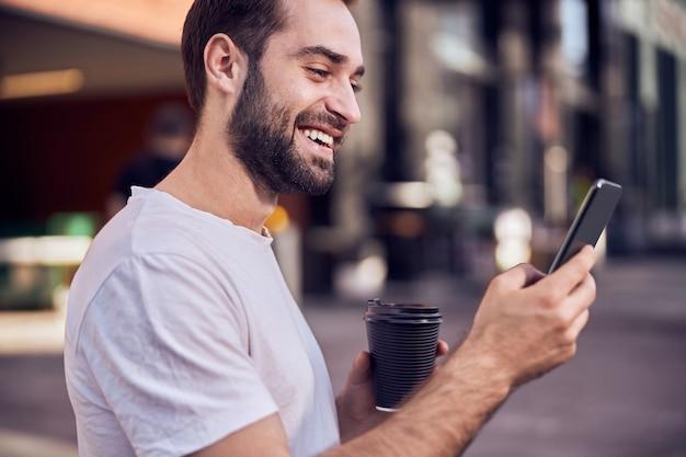 스마트 폰을 찾고 커피와 함께 재미있는 남자의 총 허리
