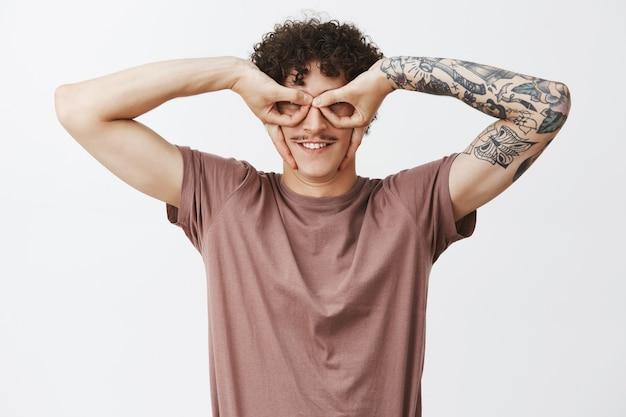 面白いと遊び心のある創造的な若い縮れ毛の男性のウエストアップショットは、入れ墨の腕と口ひげを生やして、指を大きく笑い、浮気し、灰色の壁を楽しんでアイマスクを作ります