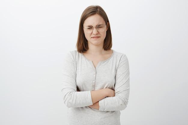Снимок талии мрачной ноющей девушки с короткой стрижкой, жалующейся на закрытие глаз и поджатых губ, скрещенных на груди с расстроенным, завистливым или ревнивым поражением в соревновании за серую стену