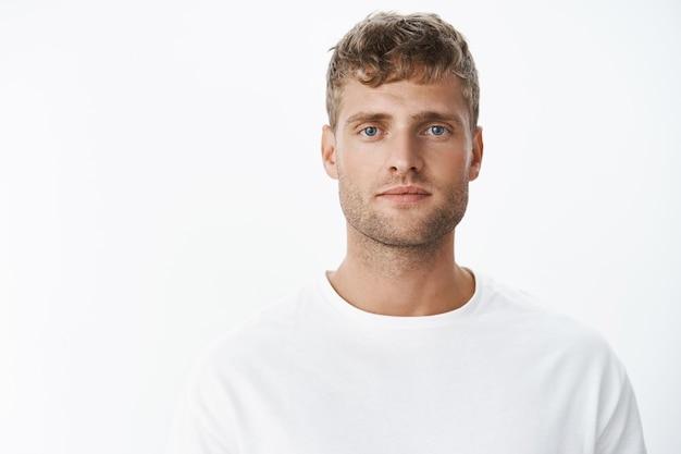 Снимок талии красивого, спокойного белокурого голубоглазого парня с щетиной в белой футболке, смотрящего вперед с расслабленным беззаботным выражением лица, позирующего над серой стеной, выглядящего искренним и спокойным