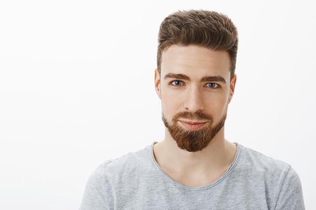 Снимок талии красивого, чувственного и уверенного в себе молодого человека с бородой, усами и голубыми глазами, улыбающегося искренним и самоуверенным, как будто с довольной улыбкой у серой стены