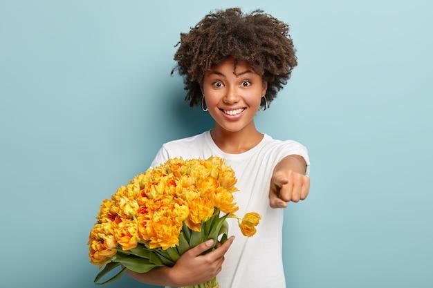 Снимок с талией счастливой красивой афро-девушки, указывающей прямо на камеру указательным пальцем, в повседневной белой футболке
