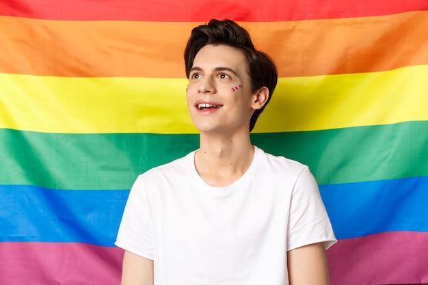 웃는 얼굴에 반짝이는 행복한 게이 남자의 허리 위로 샷, 왼쪽 상단 모서리에서 꿈꾸는 것처럼 보이며, 프라이드 휴가를 축하하고, 가시성을 위해 싸우고, lgbtq 무지개 깃발에 맞서 서 있습니다.