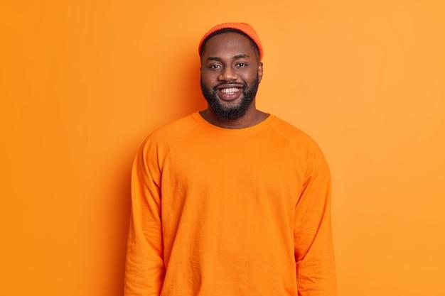 オレンジ色の帽子に身を包んだ幸せな男の笑顔のウエストアップショットと良い気分のセーターが正面を向いて明るい壁に向かってスタジオに立っているポジティブな感情を表現しています