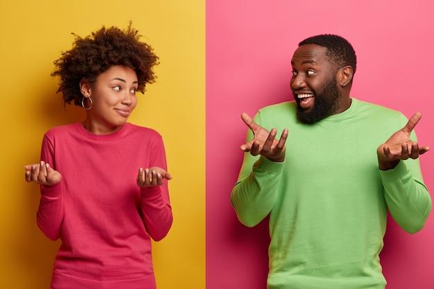 Снимок нерешительного парня и девушки, подняв вверх талию, пожимают плечами и с сомнением смотрят друг на друга, принимают решение, сталкиваются с трудным выбором, не могут решить, куда пойти в свободное время, носить яркую одежду