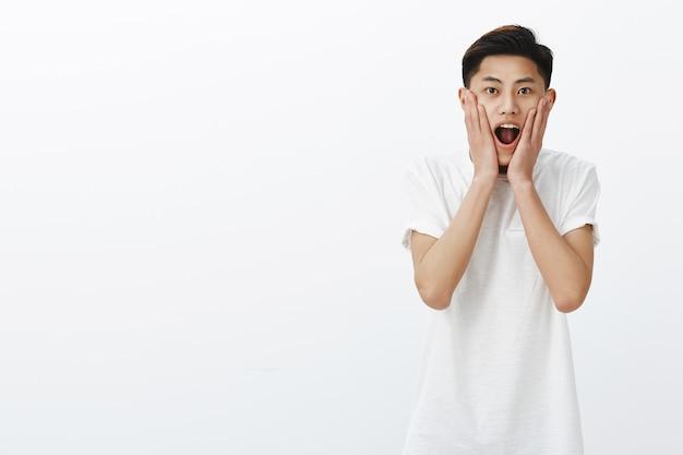 Снимок удивленного, радостного и возбужденного молодого привлекательного азиатского мужчины, который от удивления и трепета прижимает руки к щекам и удивленно реагирует на талию.