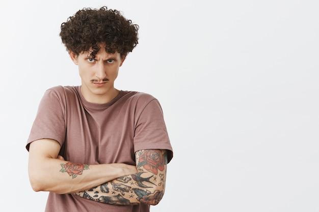 Кадр из области талии интенсивно сердитого и рассерженного молодого кудрявого мужчины с усами и татуировками, держащего в себе обиду внутри, хмурясь, глядя из-под лба, с презрением злится над серой стеной