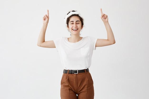 彼女の頭の上にあるコピースペースで指を指している白いtシャツを着てうれしそうな幸せな女の子のショットを上半身。手で空白の壁に何かを示す若い女性