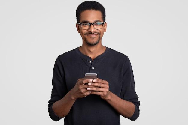 満足している陽気な暗い肌の若い男の上半身ショットスマートフォンを手に保持している、メッセージの種類、オンラインショッピング
