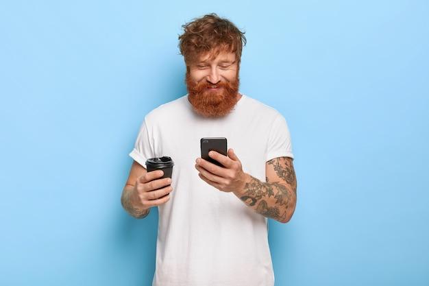 彼の携帯電話でポーズをとって喜んで笑顔の赤い髪の男のウエストアップショット