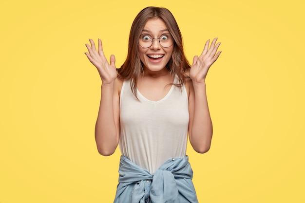 ポジティブな表情でかなり黒髪の女性のウエストアップショット、ボーイフレンドから驚きを受け取るように手を広げ、嬉しいと感じ、透明なメガネ、カジュアルなベストを着て、黄色の壁に隔離
