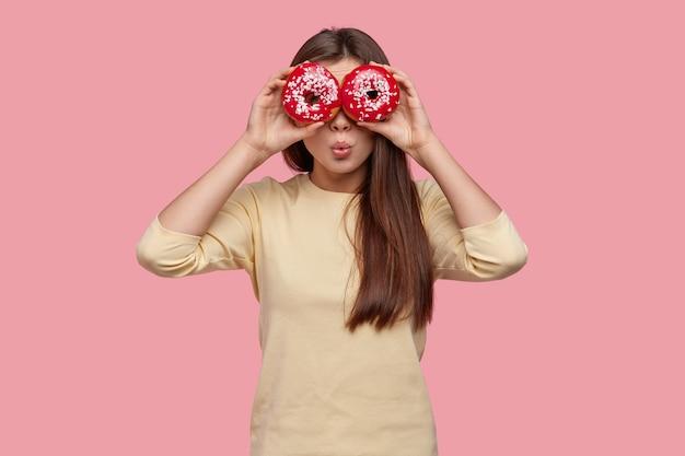 かなり若い女性のウエストアップショットは、2つの赤いドーナツで目を覆い、カジュアルな服を着て、ピンクの背景の上に立っています