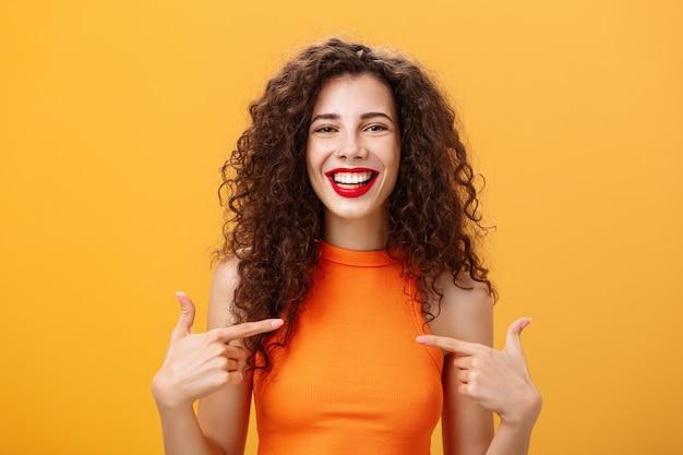 곱슬머리와 빨간 립스틱이 자신을 가리키고 있는 자랑스럽고 행복한 외향적인 매력적인 여성의 웨이스트 업 샷은 주황색 배경 위에 자신의 성취에 대해 기뻐하고 자신감 있게 이야기하고 있습니다. 복사 공간
