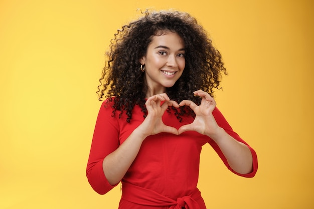 赤いドレスを着た巻き毛のロマンチックでかわいいかわいいガールフレンドのウエストアップショットは、胸にハートのサインを示し、黄色の背景の上でポーズをとって賞賛と愛を広く告白します。