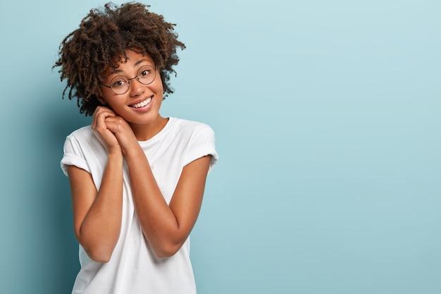 Снимок довольной темнокожей женщины с вьющейся прической, держит обе руки возле лица, имеет нежную улыбку, дружелюбное выражение лица, тронутый комплиментом, носит модели белых футболок на синей стене.