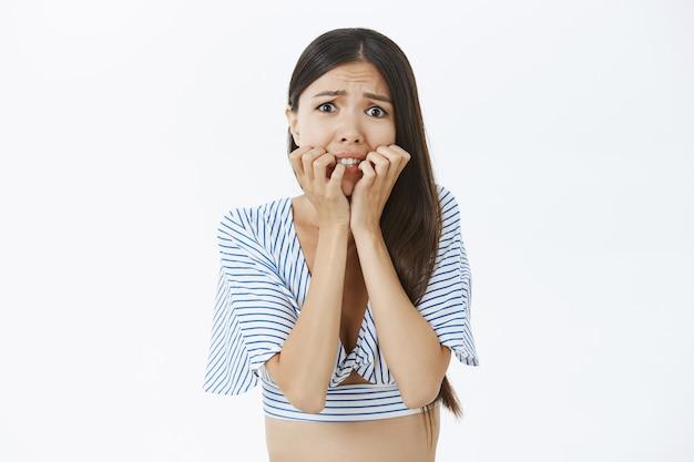 Снимок запуганной и неуверенной в себе озабоченной азиатки в укороченной блузке, кусающей пальцы и хмурящейся, дрожащей от страха