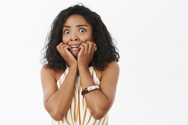 Фотография запуганной, дрожащей, неуверенной и робкой молодой темнокожей женщины с кудрявой прической.