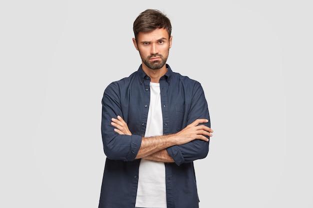 Крупным планом - серьезный небритый мужчина с уверенным выражением лица, скрестив руки, внимательно слушает необходимую информацию, носит стильную рубашку, позирует на фоне белой стены. люди, образ жизни