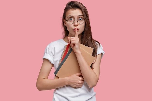 Шокированный, удивленный темноволосый студент, приподнявший талию, жестикулирует, держит указательный палец на губах, несет блокноты, одет в белую футболку