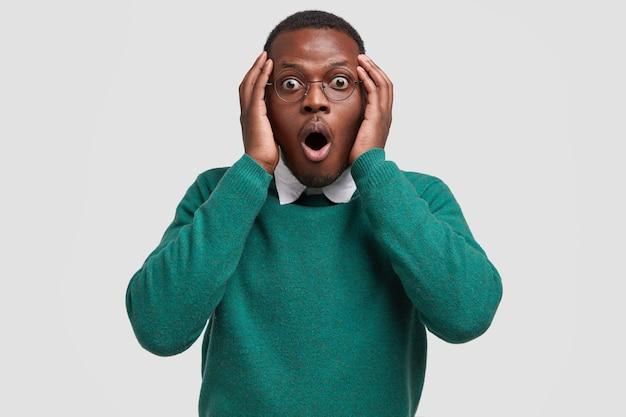 Шокированный, испуганный черный взрослый мужчина вздыхает и смотрит в ступоре, держит обе руки на голове, одетый в зеленый джемпер и белую рубашку.