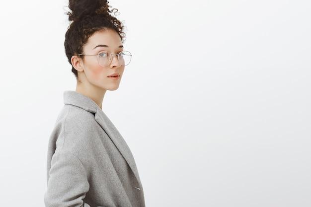 Снимок талии умной, уверенной в себе стильной девушки с вьющимися волосами, зачесанными в пучок, стоящей в профиль и смотрящей в очках