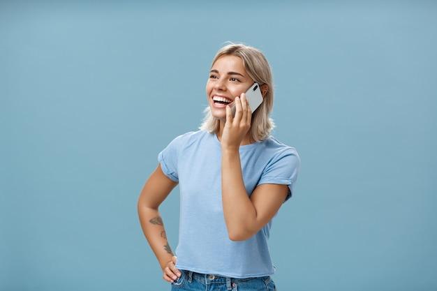 사교적이며 즐겁고 행복한 매력적인 백인 국방 머리 여자의 허리 업 샷은 스마트 폰으로 이야기하는 동안 엉덩이에 손으로 왼쪽을 응시하는 반 돌린 캐주얼 티셔츠에 서 있습니다.