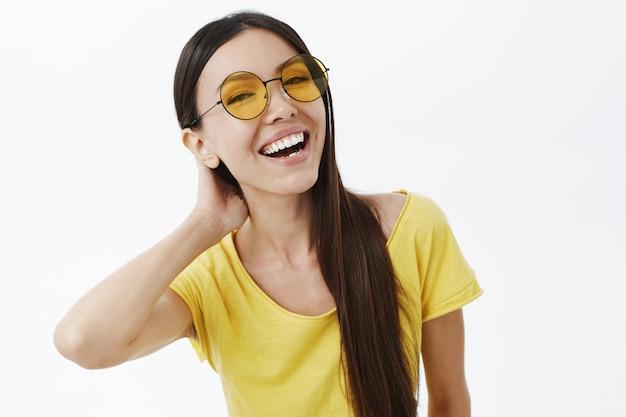 Фотография общительной беззаботной и счастливой привлекательной стройной молодой женщины в модных солнцезащитных очках и желтой футболке с талией