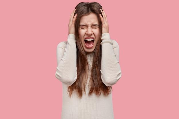 ストレスの多い絶望的なヨーロッパの女性のウエストアップショットは、イライラして悲鳴を上げ、怒って、顎を落とし続けます