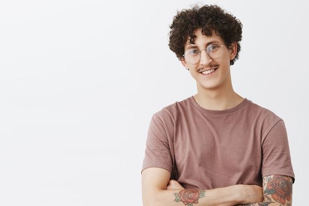 Снимок талии стильного и креативного, уверенного в себе счастливого темноволосого парня с вьющимися волосами, усами и татуированной рукой, улыбающегося с самоуверенным удовлетворенным выражением лица, гордящегося своими достижениями