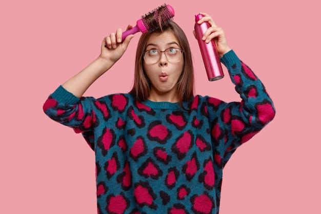 驚いたぎこちない女性のウエストアップショットはフリンジをとかし、散髪をするためのスプレー、大きな眼鏡、セーターを着ています