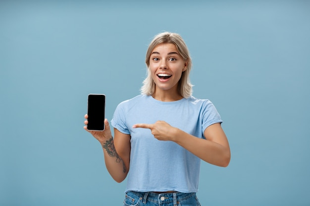 青い壁を越えて友人にインターネット経由で素晴らしい場所を示しているスマートフォンの画面を喜んで指して笑っているカジュアルなtシャツを着たスリルと感動の格好良い女子学生のウエストアップショット