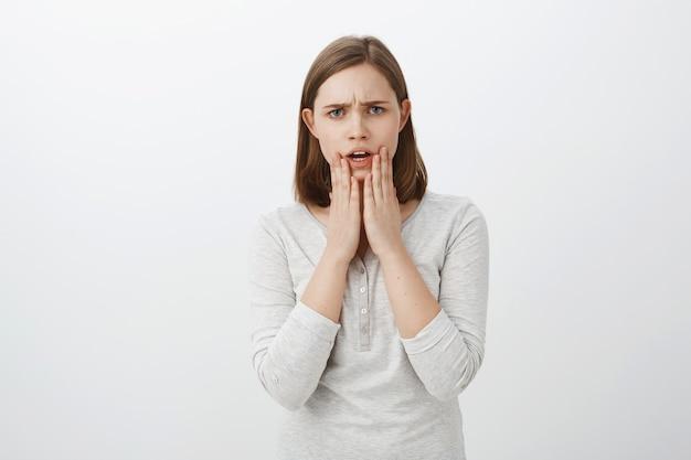 Снимок взволнованной нервной молодой брюнетки с озабоченным видом, держащий ладони на подбородке, выражающий сочувствие, когда слышит шокирующее событие, произошедшее с другом над серой стеной